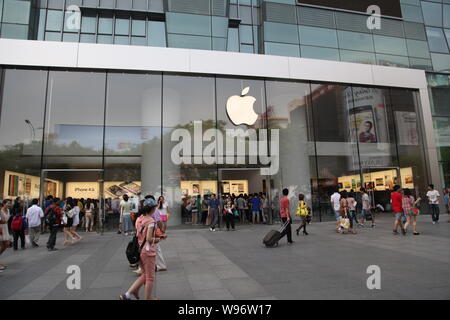 --File--Pedestrians walk past an Apple store in Beijing, China, 6 May 2012.   Apple Incs disappointing China sales suggest that its customers will not - Stock Photo