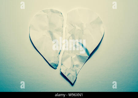 Heart symbol from old, crumpled paper, torn in half on a white vintage background. Symbol of a broken heart, unhappy love. - Stock Photo