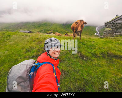 Caucasian woman tourist cyclist in helmet and raincoat takes selfie photo herself against Norwegian mountains and a funny brown cow in rainy cloudy - Stock Photo