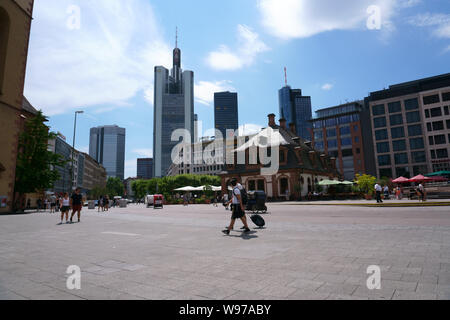 Frankfurt, Germany - July 06, 2019: Pedestrians and visitors strolling through town on the square in front of the Hauptwache with skyscrapers of the f - Stock Photo