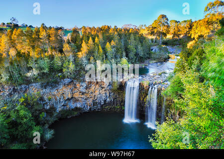 Elevated view over Dangar falls in Dorrigo National park near Dorrigo town in morning soft light with smooth water stream falling down to rock pool cu - Stock Photo