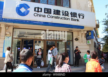 --File--Pedestrians walk past a branch of China Construction Bank (CCB) in Haerbin, northeast Chinas Heilongjiang province, 10 September 2011.   China - Stock Photo