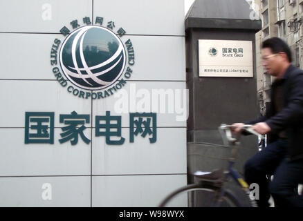 A Chinese man rides a bicycle past a branch of State Grid in Nanjing city, east Chinas Jiangsu Province, November 27, 2010.   Renaults investigation i - Stock Photo