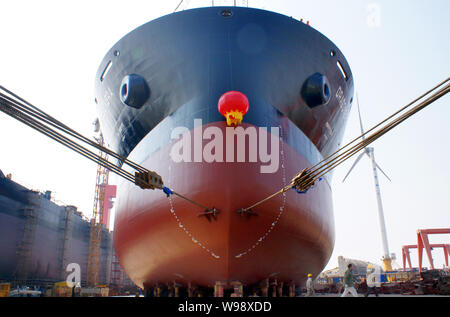 --FILE--Workers look at a bulk cargo ship to be launched at the shipyard of DDHI (Daedong Heavy Industry) in Qidong city, east Chinas Jiangsu province - Stock Photo