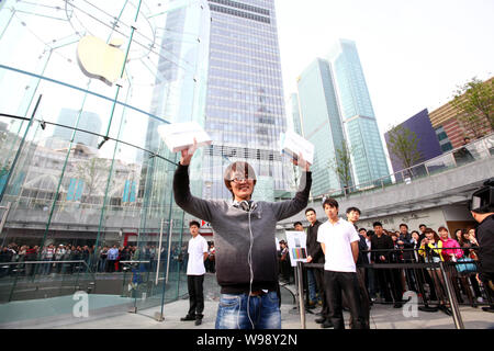 The first buyer of the iPad 2 at an Apple Store celebrates outside the store in the Lujiazui Financial District in Pudong, Shanghai, China, 6 May 2011 - Stock Photo