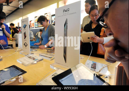 --FILE--Buyers try out iPad 2 tablet PCs at an Apple Store in Beijing, China, 6 May 2011.   A court in south China has jailed three people for stealin - Stock Photo