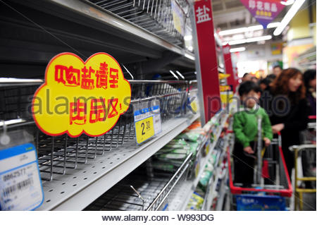 Chinese shoppers walk past empty shelves after table salt