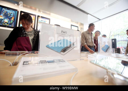 --FILE--Buyers try out iPad 2 tablet PCs at an Apple Store in Beijing, China, 5 May 2011.   A court in south China has jailed three people for stealin - Stock Photo