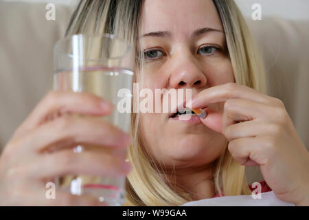 Woman taking a pill holding a water glass. Medication in capsule, concept of antibiotic, vitamin, diet, cold and flu - Stock Photo