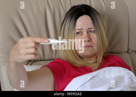 Sick woman measuring body temperature lying in a bed, digital thermometer in female hand. Concept of fever, cold and flu, illness, head pain - Stock Photo