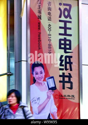--File--A pedestrian walks past an advertisement for Hanvon Technology in Shanghai, China, 6 December 2011.   Shares of Chinas biggest e-reader maker, - Stock Photo