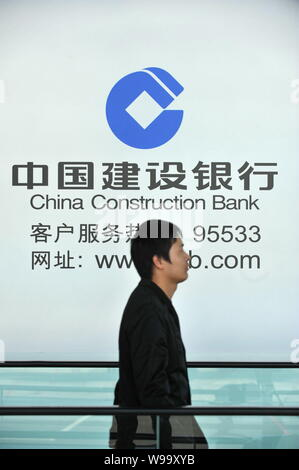 --File--A pedestrian walks past an advertisement for China Construction Bank (CCB) in Beijing, China, 28 October 2011.   Baosteel Group Corporation, t - Stock Photo