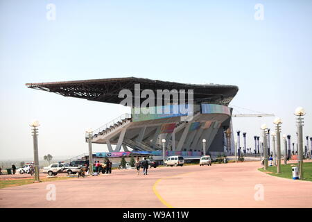 Local residents are seen near a stadium in Kangbashi New Area of Ordos city, north Chinas Inner Mongolia Autonomous Region, August 13, 2010.   It has - Stock Photo