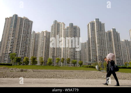 --FILE--A Chinese man carrying his luggage walks past a cluster of residential apartment buildings in Shanghai, China, 27 April 2010.   In the 13th co