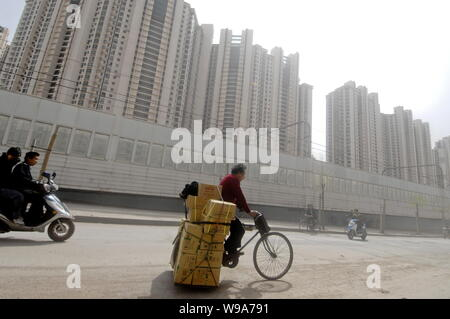 --FILE--Chinese cyclists pass by a cluster of residential apartment buildings in Shanghai, China, 27 April 2010.   In the 13th consecutive month of ye