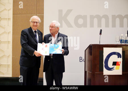 German Economy Minister Rainer Bruederle, left, is presented gifts by Mr. Manfred Knopp at a breakfast event of the German Chamber of Commerce in Shan - Stock Photo