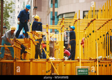 --FILE--Chinese migrant workers build scaffolding on a street in Shanghai, China, 10 September 2010.   Shanghais migrant population is on the increase - Stock Photo