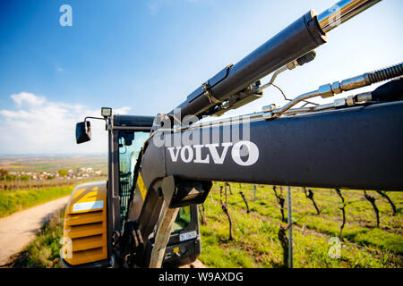Alsace, France - Apr 19, 2019: View of a new modern Volvo Ec27C Compact excavator parked in vineyard with focus on the Volvo logotype on the hydraulic arm - Stock Photo