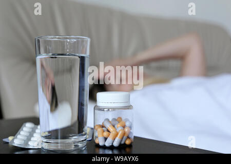 Cold and flu season, pills and water glass on background of sick woman lying in a bed. Concept of illness, fever, hot temperature - Stock Photo