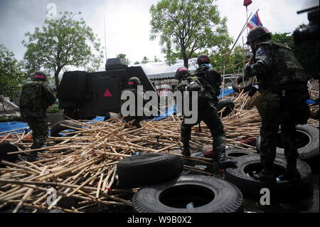 Thai soldiers move across the road-block set up by anti-government protesters on the street in Bangkok, Thailand, 19 May 2010. - Stock Photo