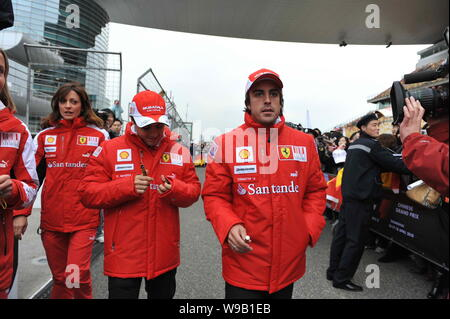Brazilian F1 driver Felipe Massa (C) and Spanish F1 driver Fernando Alonso (R) of Ferrari team are seen at the Shanghai International Circuit in Shang - Stock Photo