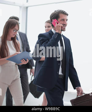 serious business man talking on smartphone while standing in office - Stock Photo