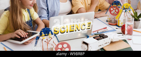 Group of kids studying on laptop with inscription Science - Stock Photo