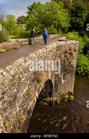 UK, England, Devon, Staverton, two male walkers crossing old stone bridge over River Dart - Stock Photo