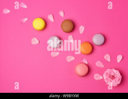 multi-colored macarons with cream and a pink rose bud with scattered petals on a pink background, top view, flat lay - Stock Photo