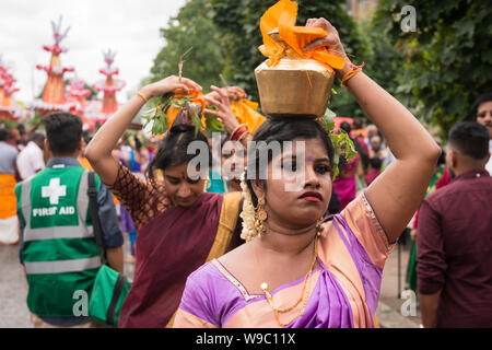 """Devotees carrying pots of milk, known as""""paal kudam, on their head during the Tamil Chariot Festival, an annual Hindu festivity, in West Ealing - Stock Photo"""
