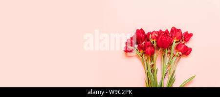 Happy Mothers day. Beautiful red tulips on pink background flat lay. Lovely greeting card with tulips for Mothers day, wedding - Stock Photo