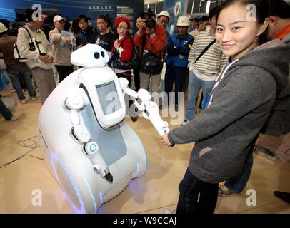 A Chinese woman shakes hands with a robot during the preparation for the China International Industry Fair 2009 in Shanghai, China, 2 November 2009. - Stock Photo