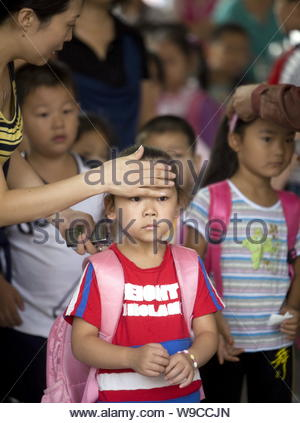 A teacher checks the temperature of pupils to identify symptoms of the H1N1 flu on the first day of their new semester at a primary school in Luoyang - Stock Photo