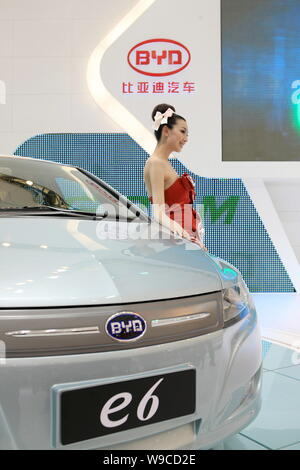 A model poses with a BYD e6 electric car at the 13th Shanghai International Automobile Industry Exhibition, known as Auto Shanghai 2009, in Shanghai, - Stock Photo