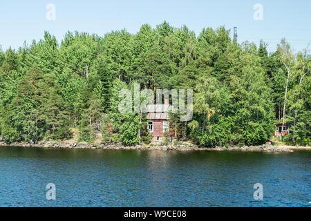 Red small finnish wooden house on island on the lake Saimaa. Lappeenranta, Finland. - Stock Photo