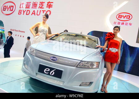 Models pose with a BYD e6 electric car at the 13th Shanghai International Automobile Industry Exhibition, known as Auto Shanghai 2009, in Shanghai, Ch - Stock Photo