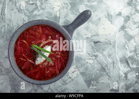 Traditional Ukrainian Russian borsch with sour cream on a bowl. A plate of red beetroot soup borsch on a gray marble background. Traditional Ukrainian - Stock Photo