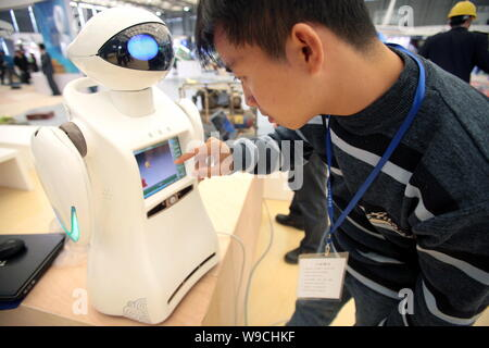 A Chinese man tests a robot during the preparation for the China International Industry Fair 2009 in Shanghai, China, 2 November 2009.   The China Int - Stock Photo