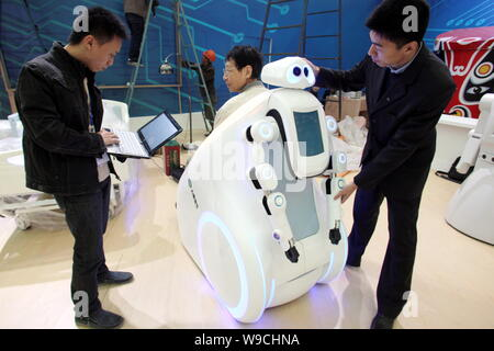 Chinese engineers test a robot during the preparation for the China International Industry Fair 2009 in Shanghai, China, 2 November 2009.   The China - Stock Photo