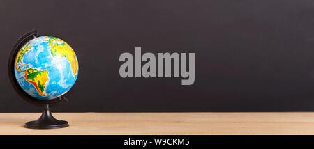 World globe on desk over chalkboard background - Stock Photo