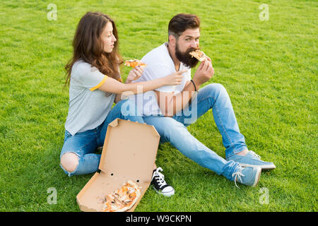 Couple eating pizza relaxing on green lawn. Fast food delivery. Bearded man and woman enjoy cheesy pizza. Couple in love dating outdoors with pizza. Hungry students sharing food. Pure enjoyment. - Stock Photo