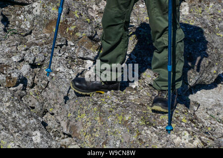 feet of a man in hiking boots with trekking poles walking in a rocky landscape - Stock Photo
