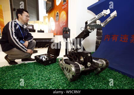 A man looks at an anti-explosion robot on display during the China International Industry Fair 2009 in Shanghai, China, 3 November 2009.   The China I - Stock Photo