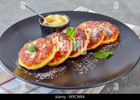 close-up of german quark Potato pancakes - Quarkkeulchen sprinkled with powdered sugar, decorated with mint leaves on a black plate with apple sauce, - Stock Photo