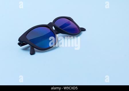 Men's trendy modern sunglasses on blue background. - Stock Photo