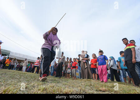Banda Aceh, Indonesia - August 17, 2018: Participants tried to put nails into bottles in the Competition to welcome Indonesia's independence day. - Stock Photo