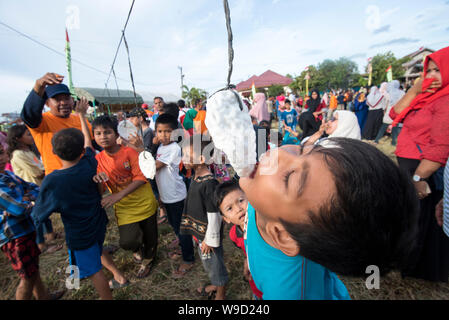 Banda Aceh, Indonesia - 17 August 2018: Participants try to eat crackers in the Crackers Eating Competition in Banda Aceh Welcoming Indonesia's - Stock Photo