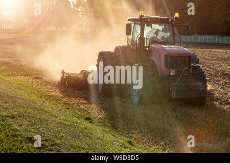 tractor cultivator plows the land, prepares for crops. dust on field - Stock Photo