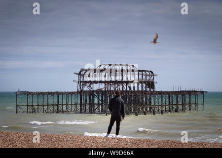 man styanding drinking beer in brighton at the pier - Stock Photo