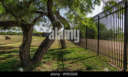 A portion of the border fence along the edge of Laredo Community College's campus in Laredo, Texas - Stock Photo